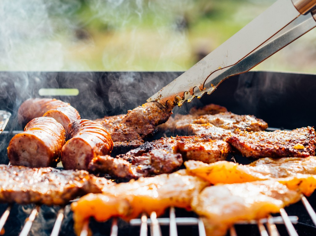 tongs with meat cooking on a barbecue