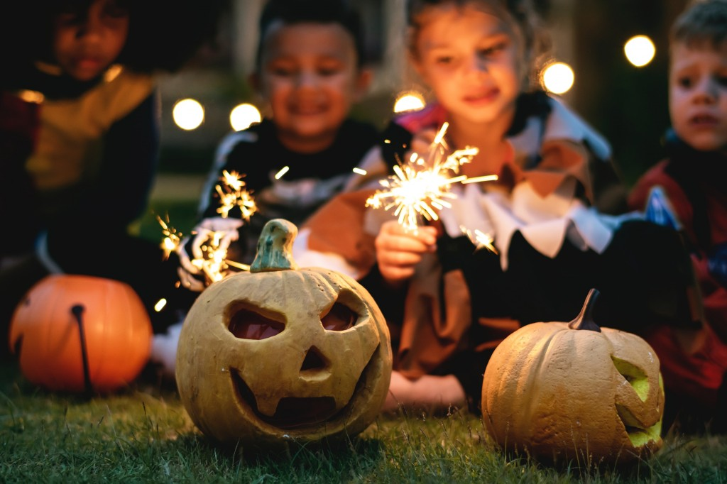 Children holding sparklers, with carved pumpkins for Halloween